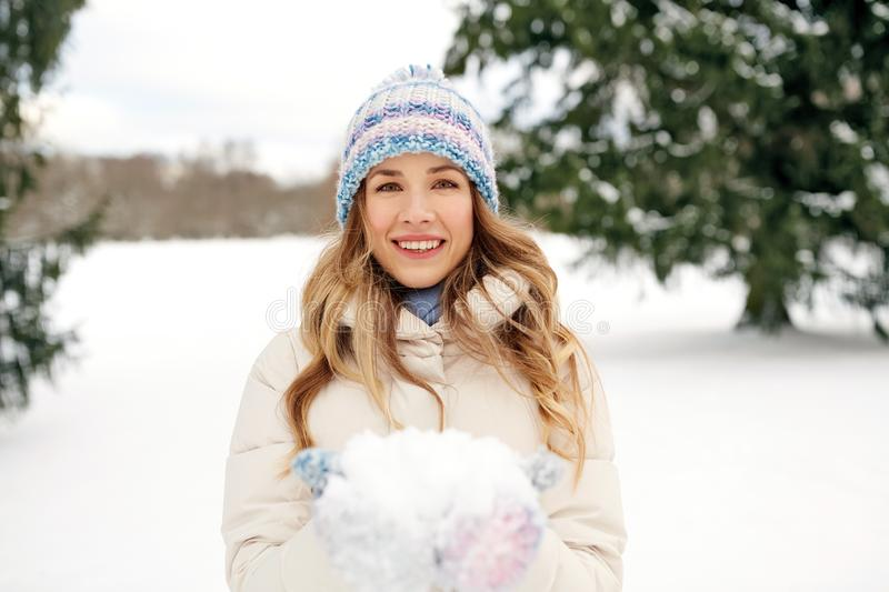 Smiling woman with snow in winter forest stock photo
