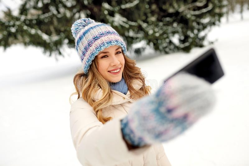 Woman taking selfie by smartphone in winter royalty free stock images