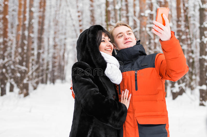People, season, love, technology and leisure concept - happy couple taking picture with smartphone on over winter royalty free stock photography