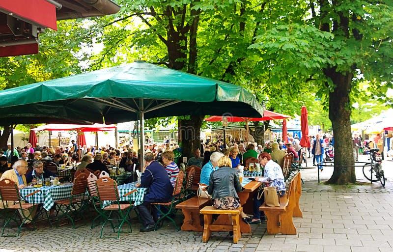 People seat at beer garden in Viktualienmarkt, gourmet point in Munich center royalty free stock image