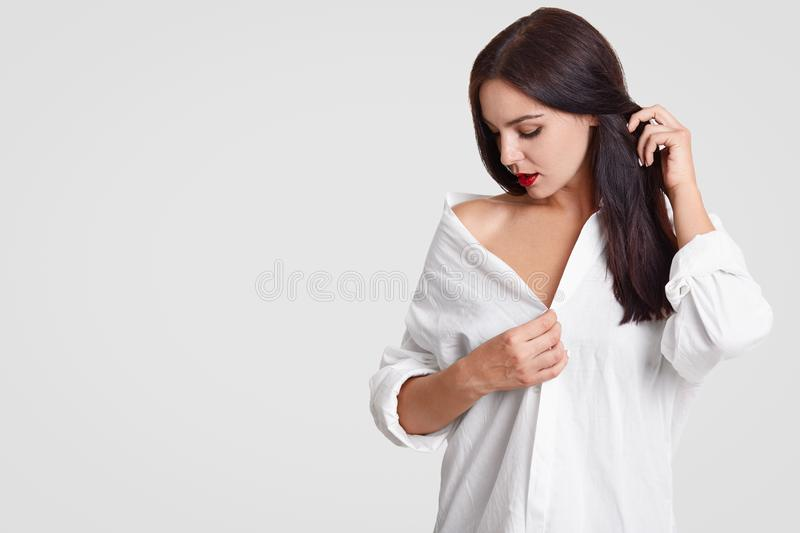 People and sensuality concept. Pensive adorable young brunette woman looks down, keeps hand on her long dark hair, wears oversized. Shirt, stands against white stock image