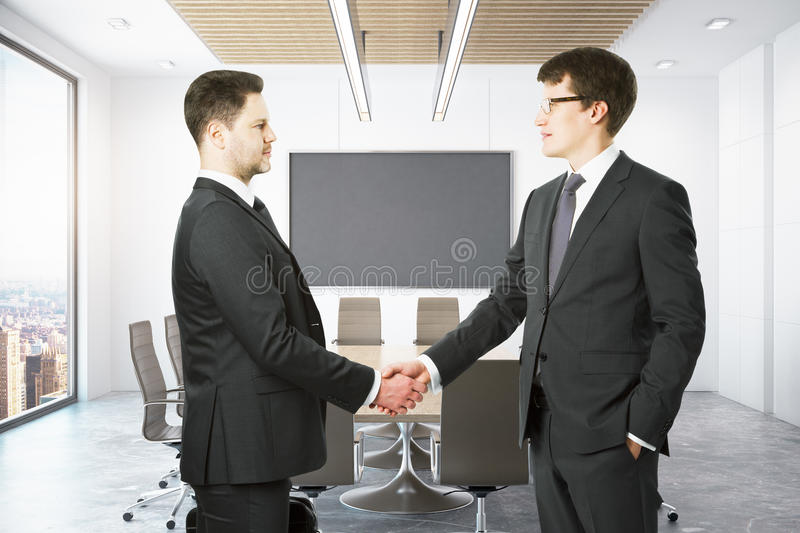 People shaking hands in conference room. Businesspeople shaking hands in modern conference room. Mock up stock images