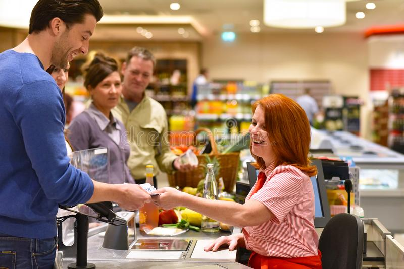 People shopping for food in the supermarket - checkout paying. Closeup royalty free stock image