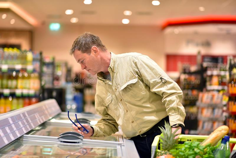 People shopping for food in the supermarket royalty free stock images