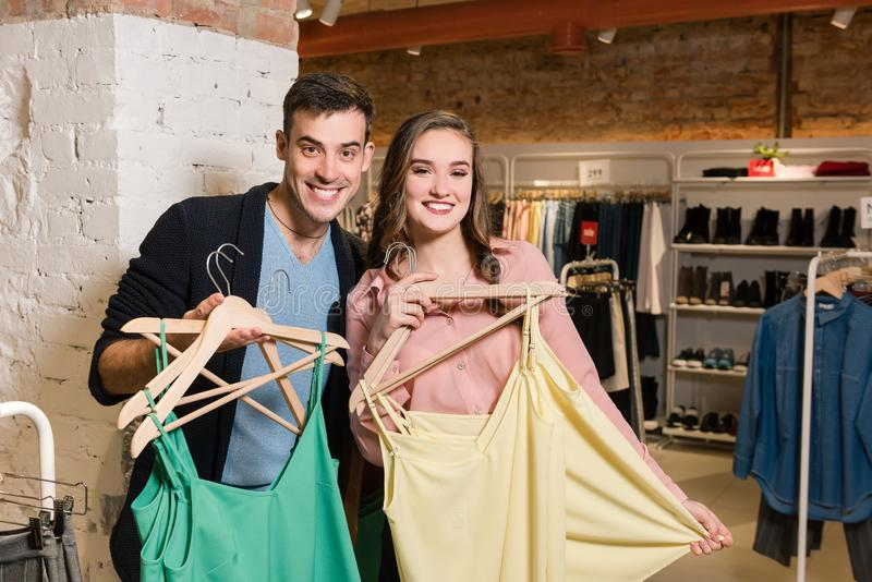 Happy smiling couple with clothes in clothes store stock photography
