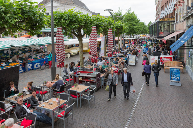People shopping at a market of Zwolle in the Netherlands. ZWOLLE, THE NETHERLANDS - MAY 30: People shopping and sitting at a terrace at a market on May 30, 2014 royalty free stock photos