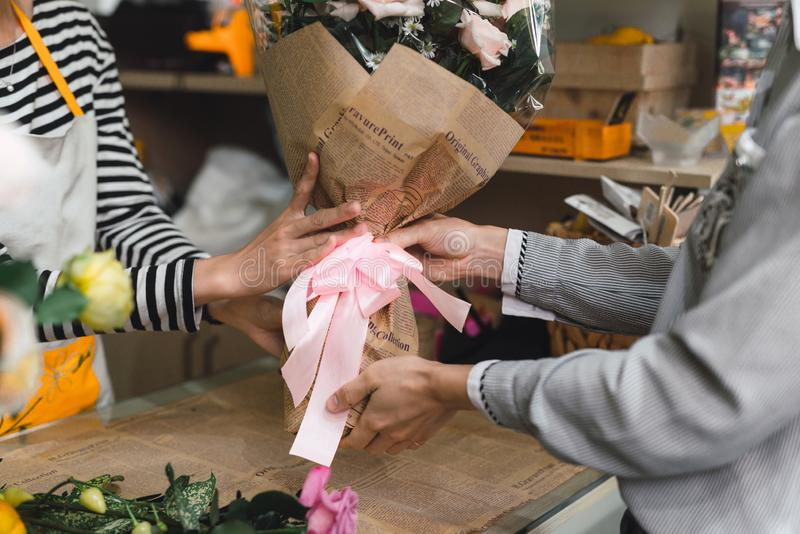 People, shopping, sale, floristry and consumerism concept - happy smiling florist woman making bouquet for and man or customer at royalty free stock images