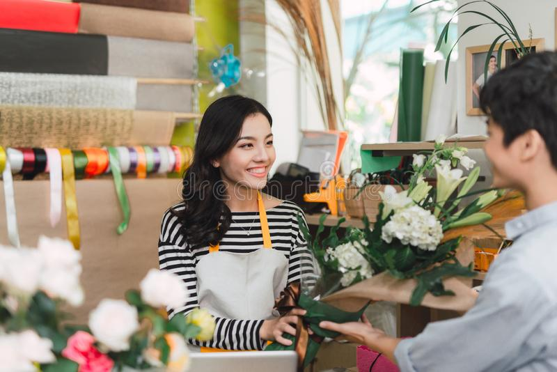 People, shopping, sale, floristry and consumerism concept - happy smiling florist woman making bouquet for and man or customer at royalty free stock photo