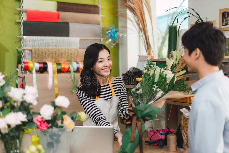 People, shopping, sale, floristry and consumerism concept - happy smiling florist woman making bouquet for and man or customer at royalty free stock photography