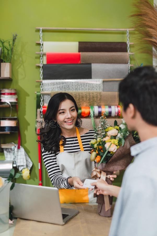 People, shopping, sale, floristry and consumerism concept - happy smiling florist woman making bouquet for and man or customer at stock photos