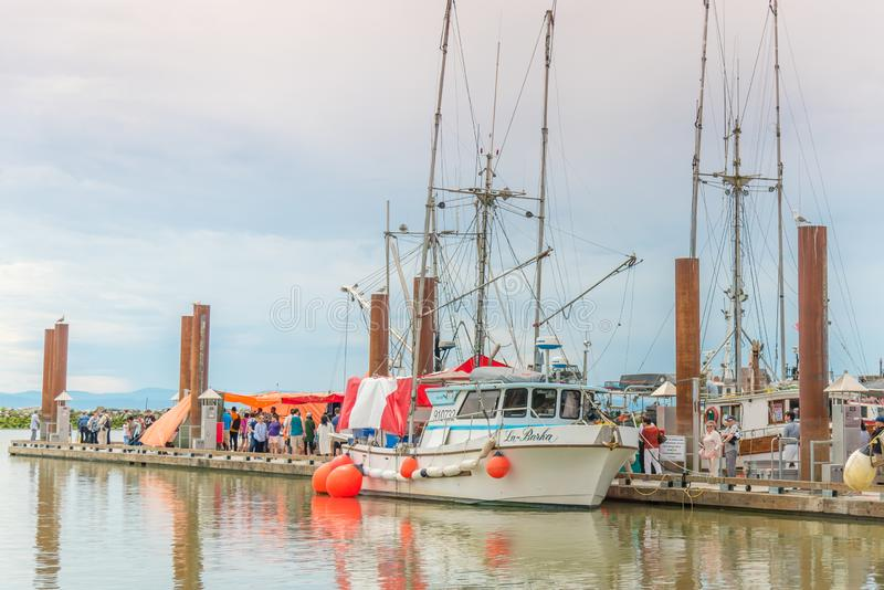 People shopping for seafood from boats docked at Fisherman`s Wharf. Steveston, British Columbia/Canada - June 24, 2018: people shopping for freshly caught royalty free stock image