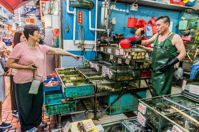 People shopping seafood market Causeway Bay Hong Kong. Causeway Bay, Hong Kong, China- June 4, 2014: people shopping at the seafood market royalty free stock images