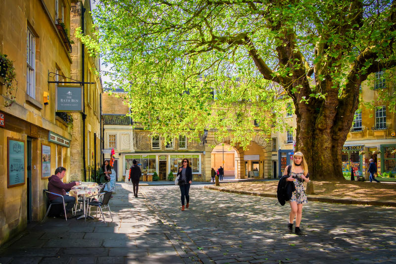 People and Shops, Courtyard, Bath England. People walk, and shop within a little square shaded by a big tree, hidden between the buildings housing restaurants royalty free stock photo