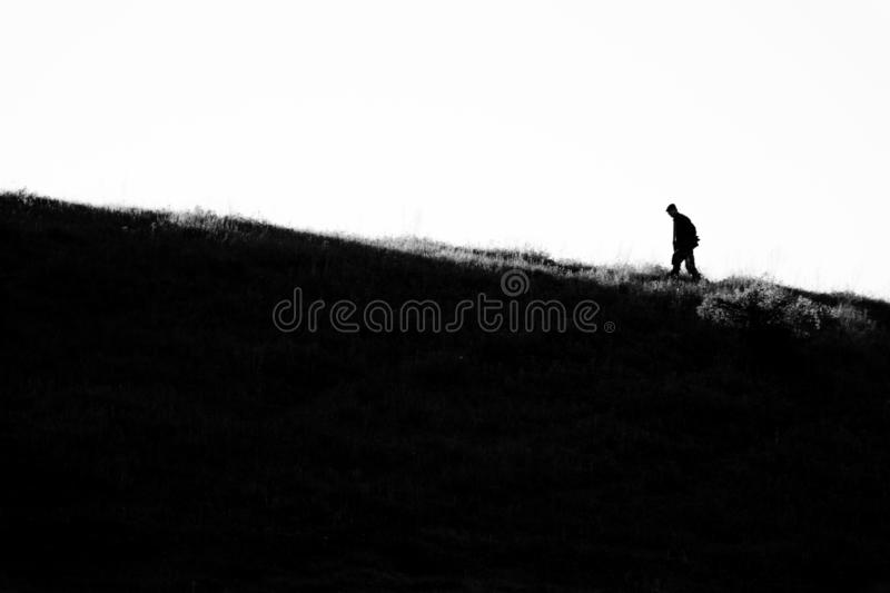 People silhouette walking up the hill. stock illustration