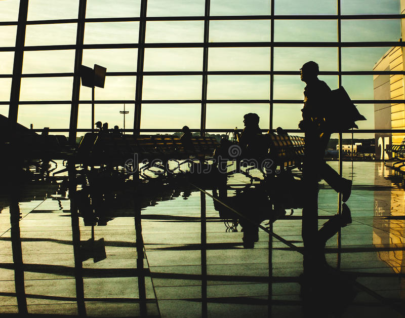 People silhouettes in airport lounge. Photo of people silhouettes in airport lounge stock images