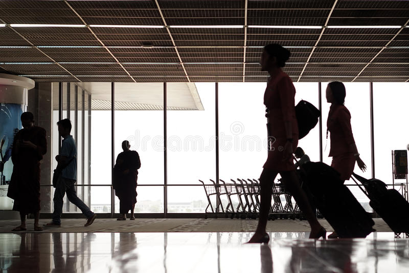 People silhouettes at airport. People silhouettes walking across terminal at airport royalty free stock image