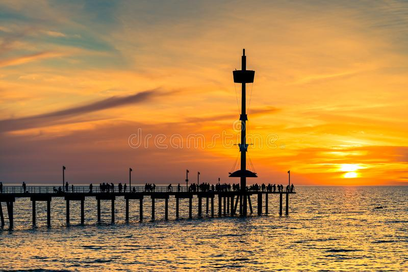 People silhouettes on Brighton Jetty at sunset royalty free stock photos