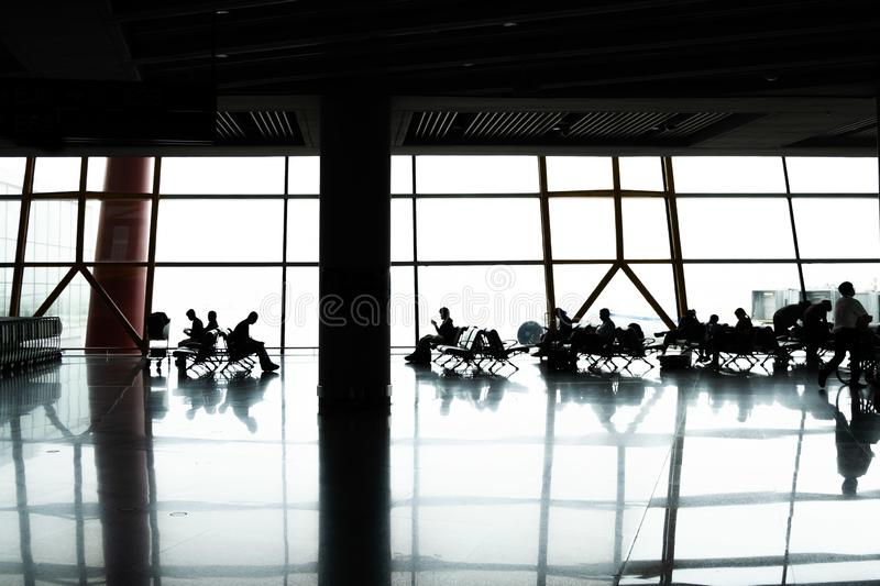 People silhouettes sitting in Airport terminal. People silhouettes sitting in Airport terminal near large window with reflections royalty free stock photos