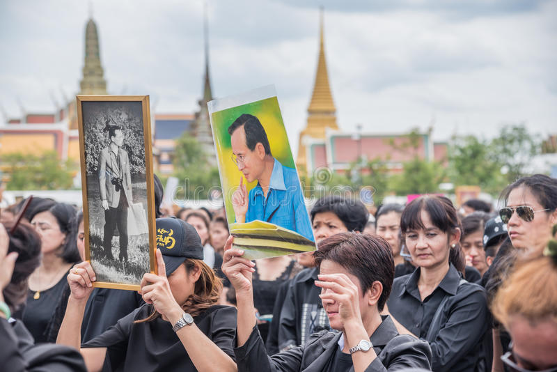 People singing the anthem and hold the portrait of Thai king. Bangkok, Thailand - October 22,2016 : Thai people singing the anthem and hold the portrait of His royalty free stock photo