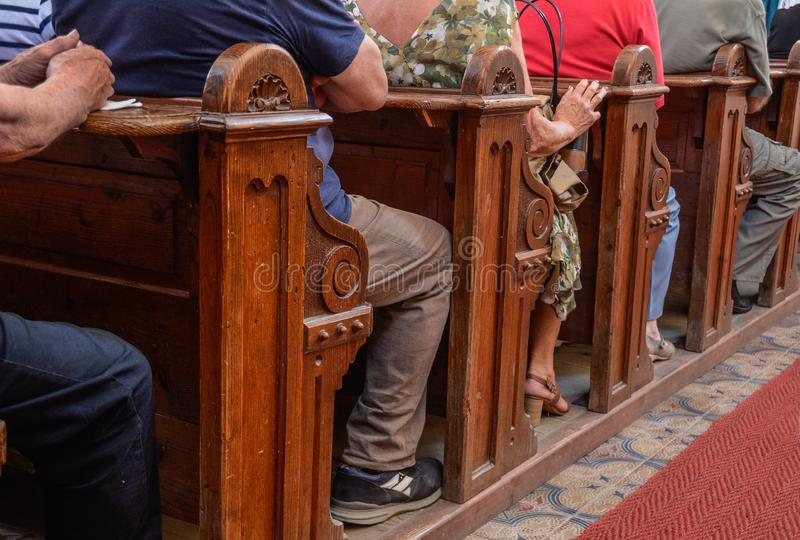 People sit in church benches religion. People sit in brown church benches. Side view of brown church benches, full of religious christian people stock image