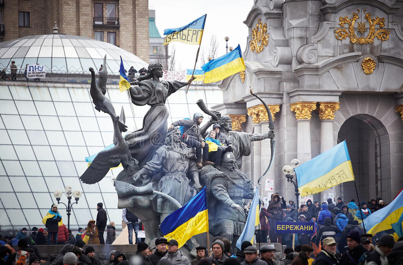 People sit on the monument decorated with flags during revolution in the Ukraine stock photos