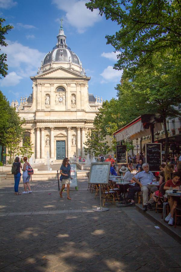 People sit at tables on the summer terrace of the cafe in front of the main entrance of university Sorbonne in Paris royalty free stock images