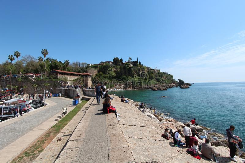People sits along the coast and look at the Mediterranean sea. Tourist port. Antalya. People sits along the coast and look at the Mediterranean sea. Tourist port stock photography