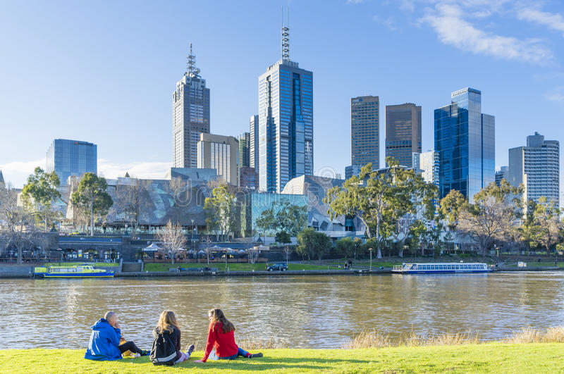 People sitting on Banks of Yarra River in Melbourne. Melbourne, Australia - August 15, 2015: People sitting on Banks of Yarra River in Melbourne near sunset with stock photo