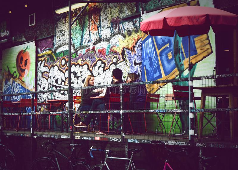 People sitting at a café in Berlin with graffiti around. Men and women at a café in Berlin in a hip area with graffiti and art royalty free stock images