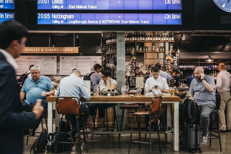 People sitting at a cafe, waiting for their trains under the departure board inside St. Pancras station, London, UK. stock photography