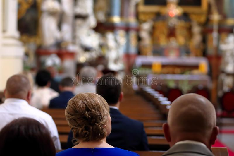 People are sitting in the church during mass. And empty space for text stock photo