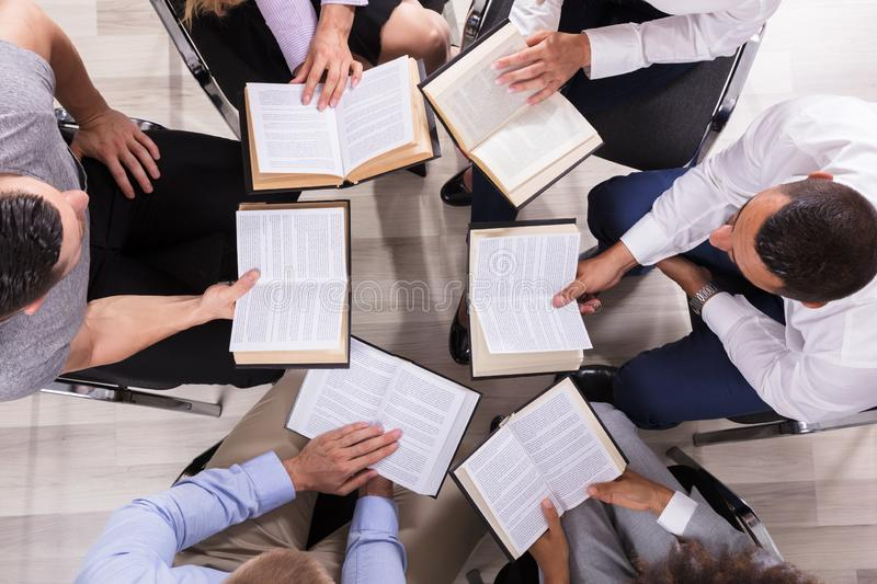 People Sitting In A Circle Reading Bible. High Angle View Of People Sitting In A Circle Reading Bible stock images