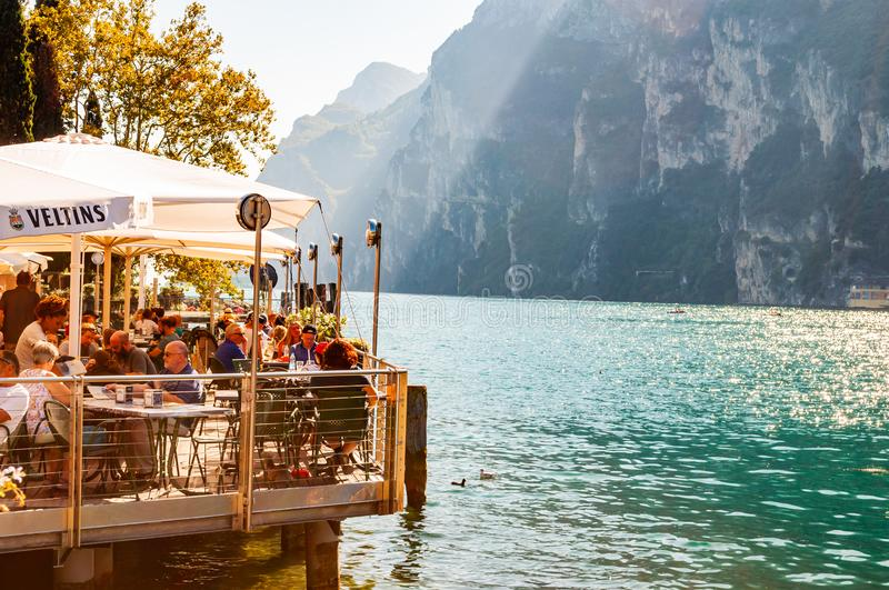 People sitting in cozy outdoor restaurant on the shore of Garda lake surrounded by high dolomite mountains with penetrating sun. Riva del Garda, Lombardy, Italy royalty free stock photos