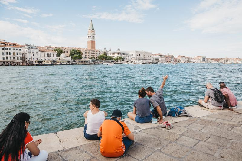 People sitting on the embankment of Grand Canal in Venice, Italy. People sitting on the embankment of Grand Canal in Venice, Italy, relaxing and admiring the stock photo