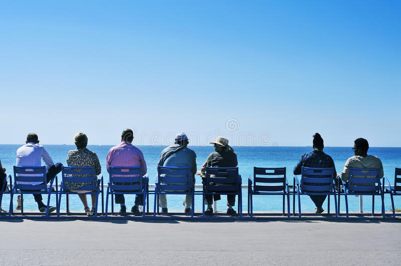 People sitting facing the sea at the Promenade des Anglais in Ni. NICE, FRANCE - MAY 16: People sitting in the characteristic blue chairs facing the royalty free stock photography