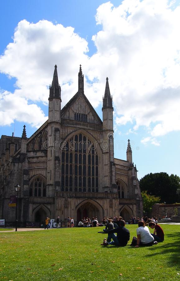 Winchester Cathedral in Southern England. People sitting on the grass outside Winchester Cathedral, one of the largest cathedrals in Europe. It is the burial stock photos