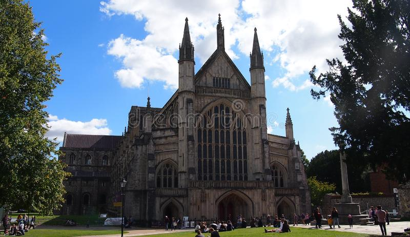Winchester Cathedral in Southern England. People sitting on the grass outside Winchester Cathedral, one of the largest cathedrals in Europe. It is the burial royalty free stock photo