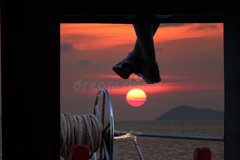 People sitting and hanging foot on the boat porch with red sky s stock photo