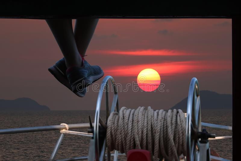 People sitting and hanging foot on the boat porch with sunset stock photos