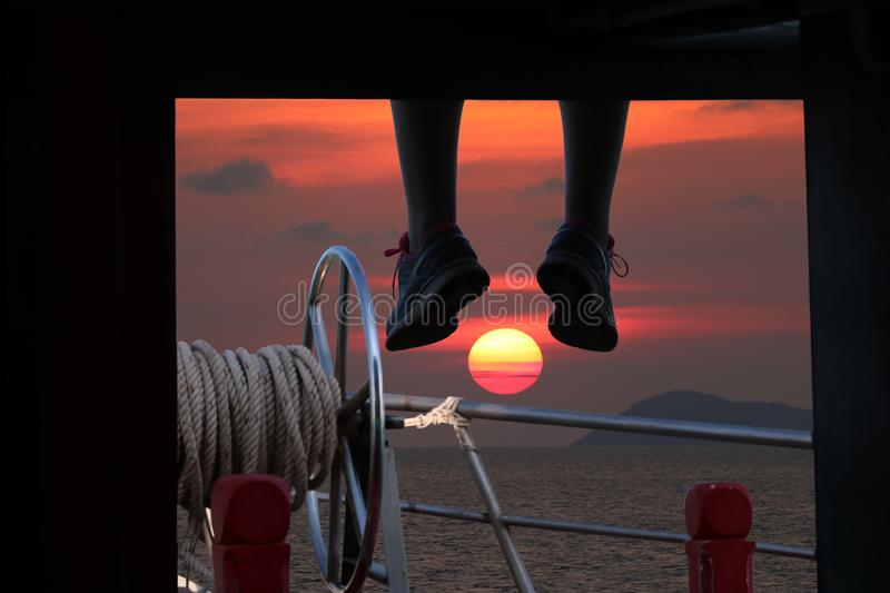 People sitting and hanging foot on the boat porch with sunset stock images