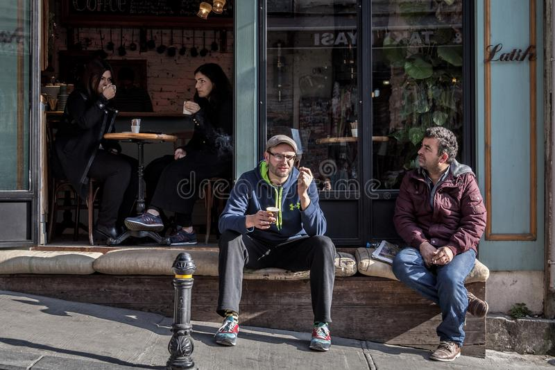 People sitting and having coffee in a coffee shop of Galata, in Karakoy district, in Beyoglu, in the European part of Istanbul. Picture of two men and two women stock photos