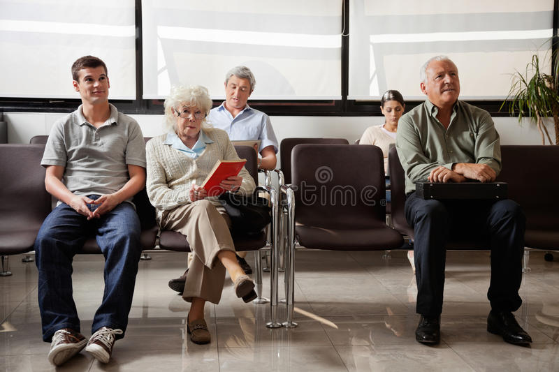 People Sitting In Hospital Lobby. Portrait of senior women with other people waiting for the doctor in hospital lobby stock photography
