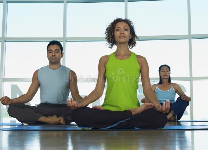 People Sitting In Lotus Position At Gym. Multiethnic people sitting in lotus position at gym royalty free stock image