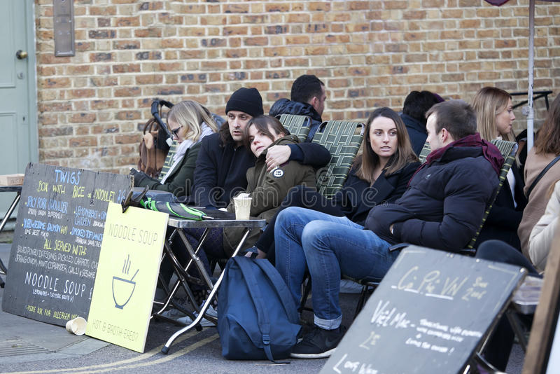 People sitting outside a cafe enjoying a beer in the cool hipster area Broadway Market. Broadway Market, London, UK - 19 June 2016: People sitting outside a cafe royalty free stock image