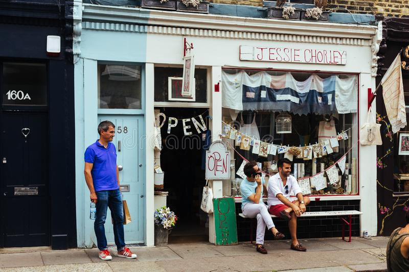 People sitting outside the souvenir shop. London, UK - July 22, 2018: people sitting outside the Jessie Chorley souvenir shop where the hand embroidery collages royalty free stock photography