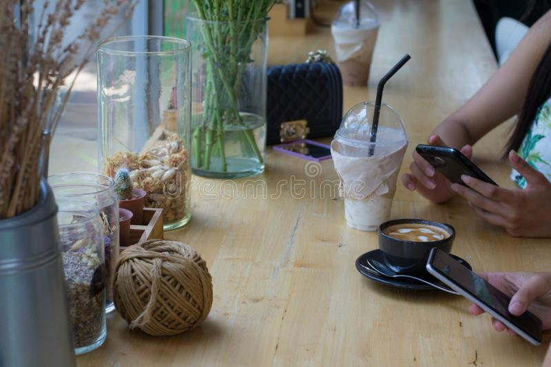 People are sitting on the phone and drinking coffee on a wooden table in a restaurant. stock images