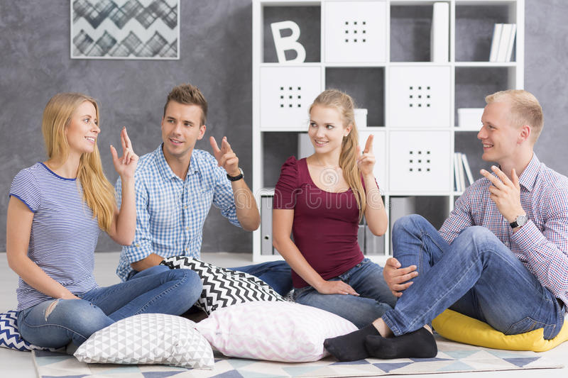 People sitting on pillows and learning sign language. Shot of smiling young people sitting on pillows and learning sign language stock photos