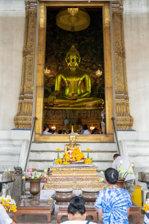 The people are sitting in prayer or religious ceremony in front of a big Buddha with the small Buddhist statues stock images