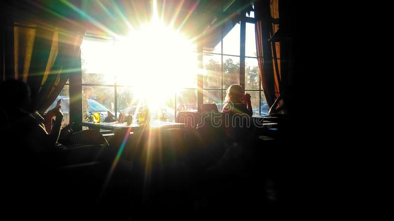 People sitting at restaurant and talking, relaxation during workday, golden hour stock photography