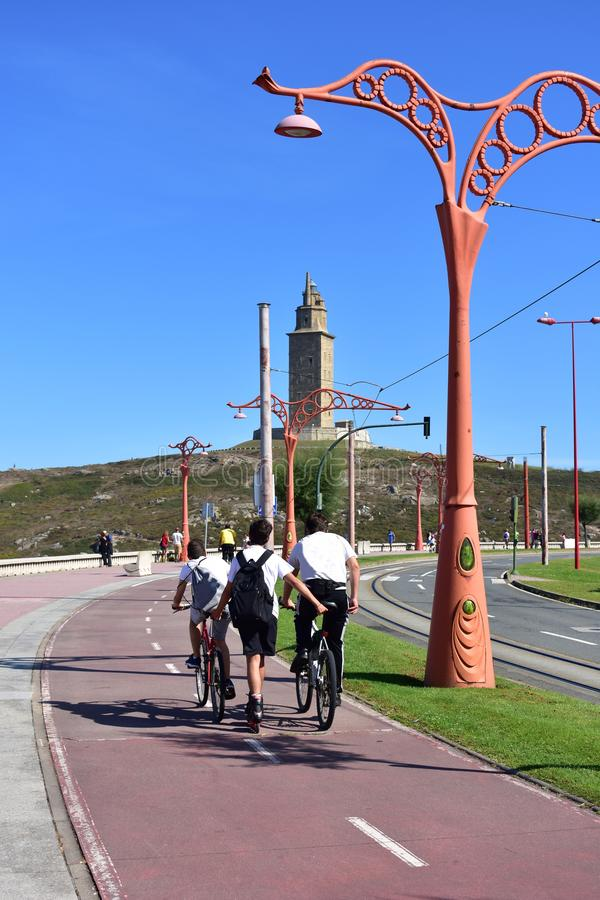 People skating and cycling in a promenade. Coastal public park with monument, grass, road, tram lines and street light. Sunny day. Young people skating and stock images